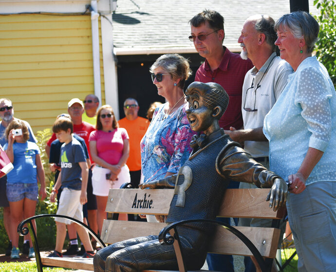 A statue of the comic strip character Archie sits on a park bench, created by sculptor Valery Mahuchy, as it was unveiled in Community Park, Meredith, Thursday, Aug. 9, 2018, as part of the town's 250th anniversary celebration. Archie illustrator Bob Montana lived in Meredith for 35 years and worked many local residents and scenes into the comic strip until his death in 1975 at age 54. Posing with the statue are Montana's children, Paige, Donald, Raymond, and Lynn. (Tom Caldwell/Laconia Daily Sun via AP)