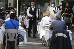 People dine out in London, Monday, Sept. 21, 2020. Britain's top medical advisers have painted a grim picture of exponential growth in illness and death if nothing is done to control the second wave of coronavirus infections, laying the groundwork for the government to announce new restrictions later this week. (AP Photo/Kirsty Wigglesworth)