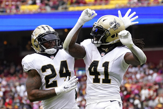 New Orleans Saints running back Alvin Kamara (41) celebrates his touchdown with teammate Dwayne Washington in the first half of an NFL football game against the Washington Football Team, Sunday, Oct. 10, 2021, in Landover, Md. (AP Photo/Alex Brandon)