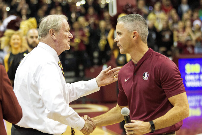 Florida State's new head football coach Mike Norvell, right, greets Florid State president John Thrasher during half time of an NCAA college basketball game against Clemson in Tallahassee, Fla., Sunday, Dec. 8, 2019. (AP Photo/Mark Wallheiser)