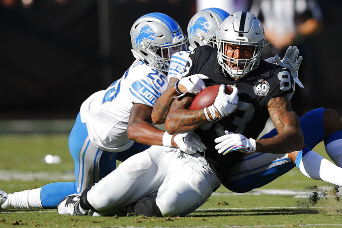 Oakland Raiders tight end Darren Waller (83) is tackled by Detroit Lions defensive back Will Harris (25) and cornerback Darius Slay during the first half of an NFL football game in Oakland, Calif., Sunday, Nov. 3, 2019. (AP Photo/John Hefti)