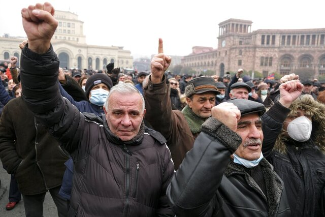 Opposition demonstrators react while listening to a speaker during a rally to pressure Armenian Prime Minister Nikol Pashinyan to resign over a peace deal with neighboring Azerbaijan in Yerevan, Armenia, Tuesday, Dec. 22, 2020. Opposition supporters in Armenia on Tuesday ramped up the pressure on the prime minister to resign over his handling of the Nagorno-Karabakh conflict with Azerbaijan, setting up a protest tent camp on the capital's main square.(Hrant Khachatryan/PAN Photo via AP)