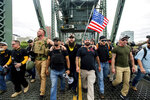 "FILE - In this Aug. 17, 2019 file photo organizer Joe Biggs, in green hat, and Proud Boys Chairman Enrique Tarrio, holding megaphone, march with members of the Proud Boys and other right-wing demonstrators march across the Hawthorne Bridge during a rally in Portland, Ore.  Proud Boys ""thought leader"" and organizer Joseph Biggs agreed to provide the FBI with information about ""Antifa networks"" in Florida and elsewhere after an agent contacted him in late July 2020 and arranged to meet at a restaurant, Biggs' lawyer, J. Daniel Hull, wrote Monday, March 29, 2021,  in a court filing. (AP Photo/Noah Berger,File)"