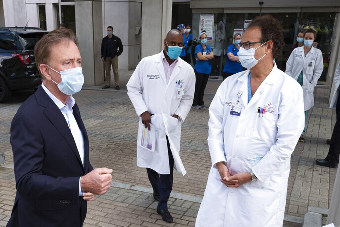 FILE - In this May 7, 2020 file photo, Connecticut Gov. Ned Lamont, left, talks with medical staff outside Saint Francis Hospital in Hartford, Conn. On Wednesday, July 8, 2020, Lamont said that the state of Connecticut has so far built up a stockpile of personal protective equipment that can last about 60 or 70 days, with plans to eventually have enough for 90 days in case there is a second wave of the coronavirus. (AP Photo/Mark Lennihan, File)
