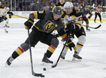 Vegas Golden Knights right wing Reilly Smith (19) skates around Boston Bruins defenseman Torey Krug (47) during the second period of an NHL hockey game Tuesday, Oct. 8, 2019, in Las Vegas. (AP Photo/John Locher)
