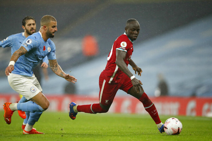 Liverpool's Sadio Mane runs with the ball past Manchester City's Kyle Walker, left, during the English Premier League soccer match between Manchester City and Liverpool at the Etihad stadium in Manchester, England, Sunday, Nov. 8, 2020. (Clive Brunskill/Pool via AP)