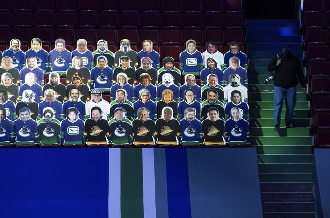 Cardboard cutouts of fans are displayed in the seats before an NHL hockey game between the Vancouver Canucks and the Toronto Maple Leafs in Vancouver, British Columbia, Sunday, April 18, 2021. (Darryl Dyck/The Canadian Press via AP)