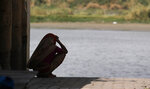 A woman sits in the shade on the banks of the river Yamuna in New Delhi, India, Thursday, May 28, 2020. India grappled with scorching temperatures and the worst locust invasion in decades as authorities prepared for the end of a months long lockdown despite recording thousands of new infections every day. (AP Photo/Manish Swarup)