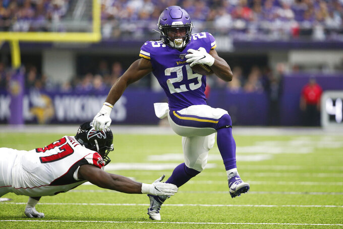 Minnesota Vikings running back Alexander Mattison (25) breaks a tackle by Atlanta Falcons defensive tackle Grady Jarrett, left, during the first half of an NFL football game Sunday, Sept. 8, 2019, in Minneapolis. (AP Photo/Bruce Kluckhohn)