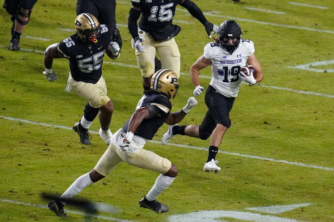 Northwestern wide receiver Riley Lees (19) tries to get past Purdue safety Marvin Grant (4) after a catch during the first half of an NCAA college football game in West Lafayette, Ind., Saturday, Nov. 14, 2020. (AP Photo/Michael Conroy)