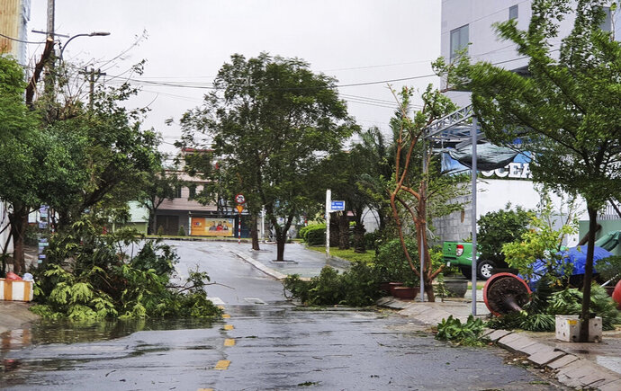 Broken tree branches caused by strong winds from typhoon Molave lie on a deserted street in Da Nang, Vietnam Wednesday, Oct. 28, 2020. Typhoon Malove sank a few fishing boats as it approached Vietnam's south central coast on Wednesday morning. (Vo Van Dung/VNA via AP)