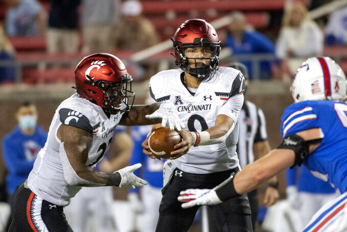Cincinnati quarterback Desmond Ridder (9) hands off to running back Gerrid Doaks (23) during the second half of an NCAA college football game against SMU Saturday, Oct. 24, 2020, in Dallas. (AP Photo/Jeffrey McWhorter)