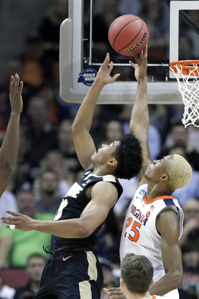 Virginia's Mamadi Diakite (25) blocks the shot of Purdue's Nojel Eastern during the first half of the men's NCAA Tournament college basketball South Regional final game, Saturday, March 30, 2019, in Louisville, Ky. (AP Photo/Michael Conroy)