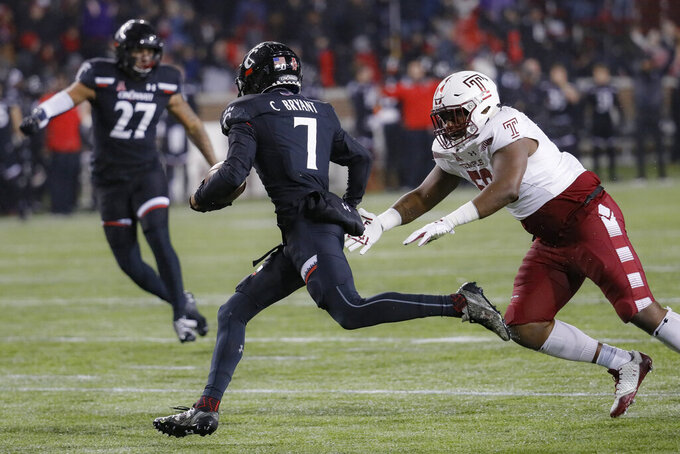Cincinnati cornerback Coby Bryant (7) picks up a blocked extra point attempt by Temple place kicker Will Mobley before returning it for a touchdown during the second half of an NCAA college football game, Saturday, Nov. 23, 2019, in Cincinnati. (AP Photo/John Minchillo)