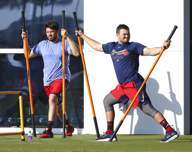 Atlanta Braves catchers Travis D'Arnaud, left, and Shea Langeliers do agility drills to loosen up for baseball spring training Sunday, Feb. 16, 2020, in North Port, Fla. (Curtis Compton/Atlanta Journal-Constitution via AP)