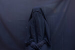 In this Sept. 9, 2019 photo, Yazidi Layla Taloo poses for a portrait in the full-face veil and abaya she wore while enslaved by Islamic State militants, at her home in Sharia, Iraq. Taloo's 2 1/2-year ordeal in captivity underscores how IS members continually ignored the rules the group tried to impose on the slave system.