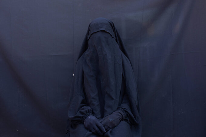 "In this Sept. 9, 2019 photo, Yazidi Layla Taloo poses for a portrait in the full-face veil and abaya she wore while enslaved by Islamic State militants, at her home in Sharia, Iraq. Taloo's 2 1/2-year ordeal in captivity underscores how IS members continually ignored the rules the group tried to impose on the slave system. ""They explained everything as permissible. They called it Islamic law. They raped women, even young girls,"" said Taloo, who was owned by eight men. (AP Photo/Maya Alleruzzo)"