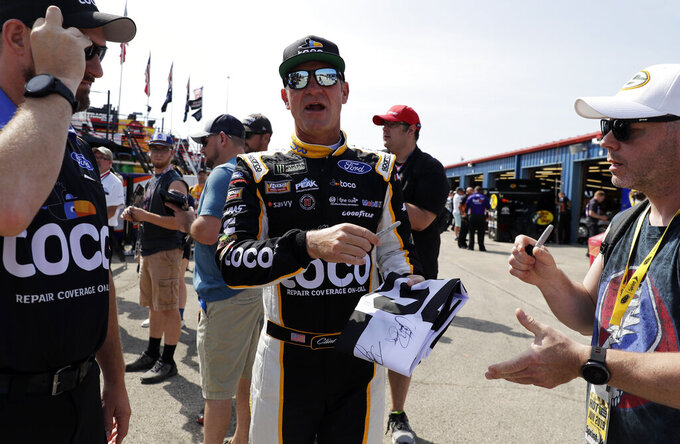 Clint Bowyer, center, talks with fans during a practice for the NASCAR Sprint Cup Series auto race at Chicagoland Speedway in Joliet, Ill., Saturday, June 29, 2018. (AP Photo/Nam Y. Huh)