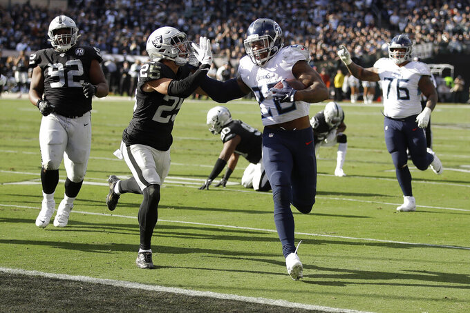 Tennessee Titans running back Derrick Henry (22) scores past Oakland Raiders free safety Erik Harris (25) during the first half of an NFL football game in Oakland, Calif., Sunday, Dec. 8, 2019. (AP Photo/Ben Margot)