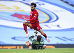 Liverpool's Mohamed Salah leaps over Manchester City's goalkeeper Ederson during the English Premier League soccer match between Manchester City and Liverpool at Etihad Stadium in Manchester, England, Thursday, July 2, 2020. (AP Photo/Laurence Griffiths,Pool)