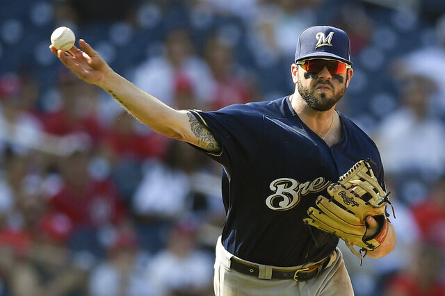 FILE - In this Aug. 18, 2019, file photo, Milwaukee Brewers third baseman Mike Moustakas throws the ball to first during a baseball game against the Washington Nationals in Washington. All-Star infielder Moustakas and the Cincinnati Reds have agreed to a $64 million, four-year contract, a person familiar with the negotiations told The Associated Press. The person spoke on condition of anonymity Monday, Dec. 2, 2019, because the agreement had not been announced. (AP Photo/Nick Wass, File)
