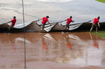 Grounds crew pulls the tarp to cover the baseball diamond from a heavy downpour delaying the baseball game during the sixth inning of a baseball game between the Washington Nationals and the Baltimore Orioles in Washington, Sunday, Aug. 9, 2020. (AP Photo/Manuel Balce Ceneta)