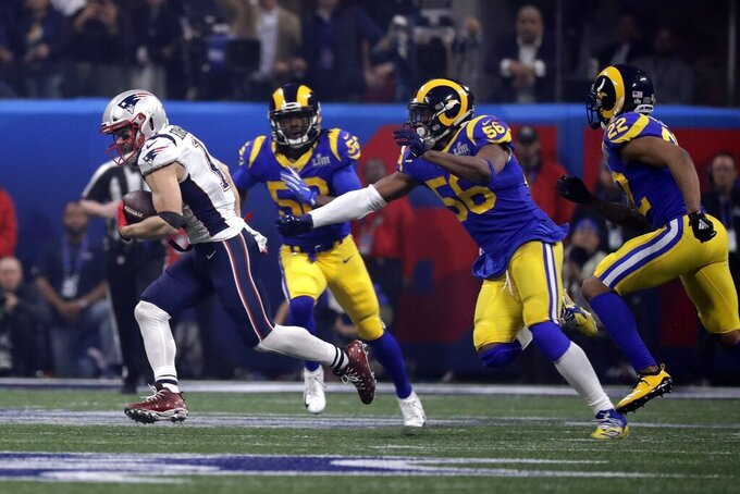 New England Patriots' Julian Edelman, left, runs from Los Angeles Rams' Cory Littleton (58), Dante Fowler (56) and Marcus Peters (22) during the second half of the NFL Super Bowl 53 football game Sunday, Feb. 3, 2019, in Atlanta. (AP Photo/Chuck Burton)