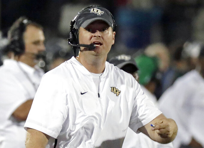 "FILE - In this Sept. 21, 2018, file photo, Central Florida head coach Josh Heupel directs his team against Florida Atlantic during the second half of an NCAA college football game n Orlando, Fla. No. 11 UCF, heavily favored to beat Navy to remain unbeaten and extend the nation's longest winning streak to 22 games, insists the Knights aren't paying attention to chatter about their chances of winding up in the College Football Playoff. ""We talk about it every day. ... Outside noise has no impact on what we are,""  Heupel reiterated.  (AP Photo/John Raoux, File)"