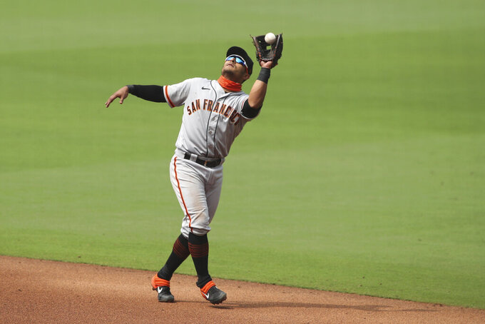 FILE-  In this Sept. 13, 2020, file photo, San Francisco Giants second basemen Donovan Solano catches an infield pop fly by a San Diego Padres batter during a baseball game in San Diego. The Giants defeated Solano in salary arbitration Thursday, Feb. 18, and the infielder will be paid the team's $3.25 million offer rather than his $3.9 million request. (AP Photo/Derrick Tuskan, File)
