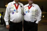 This July 4, 2019 photo shows Tom Earle, left, and Peter Brych, from the Triangle Squares club in Toronto, posing with their name badges and medallions for each year they've attended the IAGSDC conference, in Philadelphia. The 36th annual International Association of Gay Square Dance Clubs convention was held in Philadelphia over the Fourth of July holiday weekend. (AP Photo/Jacqueline Larma)