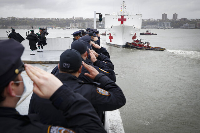 NYPD officers salute the USNS Naval Hospital Ship Comfort as it is pushed out into the Hudson River by tugboats, Thursday, April 30, 2020, in the Manhattan borough of New York. (AP Photo/John Minchillo)