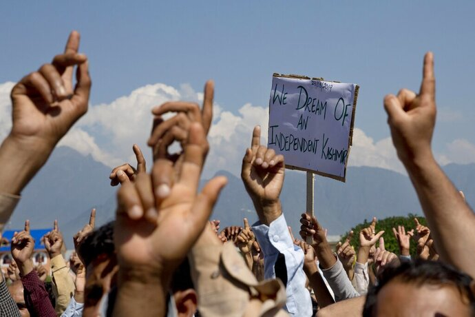 FILE - In this Friday, Aug. 23, 2019, file photo, Kashmiri men shout freedom slogans during a protest against New Delhi's tightened grip on the disputed region, after Friday prayers on the outskirts of Srinagar, Indian controlled Kashmir. India's Home Minister Amit Shah says normalcy has returned in most areas in Indian-controlled Kashmir but the detention of politicians and the blockade of the internet and social media are continuing because of security concerns. Asked by lawmakers in Parliament on Wednesday, Nov. 20, how soon the restrictions are likely to be lifted, Shah says authorities have to fix priorities when it comes to security and the fight against terrorism. India stripped the region of its semi-autonomous powers and implemented a strict clampdown on Aug. 5. (AP Photo/ Dar Yasin, File)