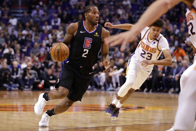 Los Angeles Clippers forward Kawhi Leonard (2) drives as Phoenix Suns forward Cameron Johnson (23) pursues during the first half of an NBA basketball game, Wednesday, Feb. 26, 2020, in Phoenix. (AP Photo/Matt York)