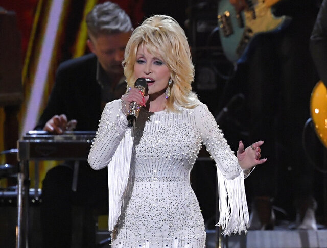 FILE - This Nov. 13, 2019 file photo shows Dolly Parton performing at the 53rd annual CMA Awards in Nashville, Tenn. Parton tweeted Wednesday, April 1, that she's donating $1 million to Vanderbilt University Medical Center in Nashville, Tennessee for coronavirus research.   (AP Photo/Mark J. Terrill, File)