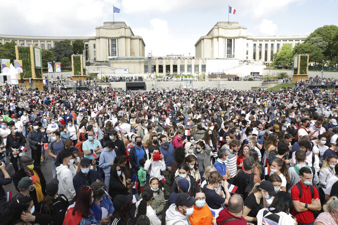 People gather in the Olympics fan zone at the Trocadero in Paris, Sunday, Aug. 8, 2021. A giant flag will be unfurled on the Eiffel Tower in Paris Sunday as part of the handover ceremony of Tokyo 2020 to Paris 2024, as Paris will be the next Summer Games host in 2024. The passing of the hosting baton will be split between the Olympic Stadium in Tokyo and a public party and concert in Paris. (AP Photo/Adrienne Surprenant)