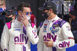 Teammates Simon Pagenaud, left, of France, and Jimmie Johnson talk on pit road before the start of the Rolex 24 hour auto race at Daytona International Speedway, Saturday, Jan. 30, 2021, in Daytona Beach, Fla. (AP Photo/John Raoux)