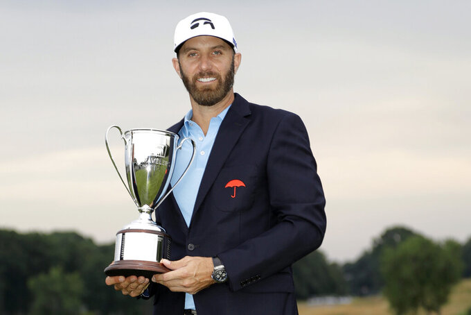 FILE — In this June 28, 2020, file photo, Dustin Johnson poses with the trophy after winning the Travelers Championship golf tournament at TPC River Highlands, Sunday, in Cromwell, Conn. Johnson says it was surreal sinking the final putt to win last year's Travelers Championship with fewer than 40 spectators politely clapping instead of the thousands that usually fill the bowl surrounding the 18th green at TPC River Highlands. (AP Photo/Frank Franklin II, File)