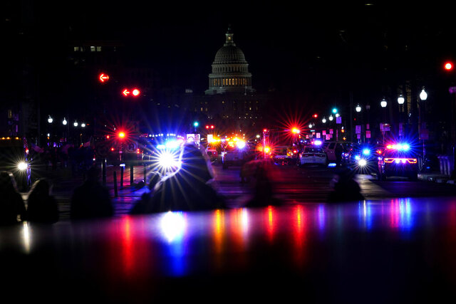 FILE - In this Wednesday, Jan. 6, 2021, file photo, with the U.S. Capitol in the background, lights from police vehicles illuminate Pennsylvania Avenue in Washington, following an insurrection. Federal agents have accused an Arkansas man of beating a police officer with a pole flying a U.S. flag during the Jan. 6 riot at the U.S. Capitol. (AP Photo/Carolyn Kaster, File)