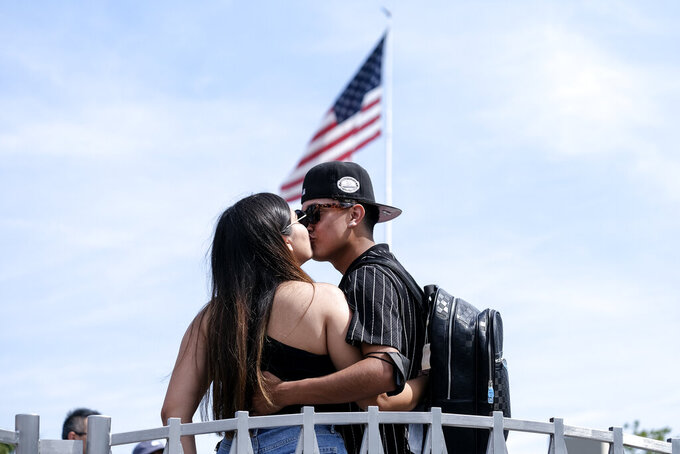 """Silvia Guillen, 19, and her boyfriend Joseph Alvarez, 22, both from El Paso, Texas, share a kiss at Universal Studios in Universal City, Calif., Tuesday, June 15, 2021.  On Tuesday, California lifted most of its COVID-19 restrictions and ushered in what has been billed as the state's """"Grand Reopening."""" (AP Photo/Ringo H.W. Chiu)"""