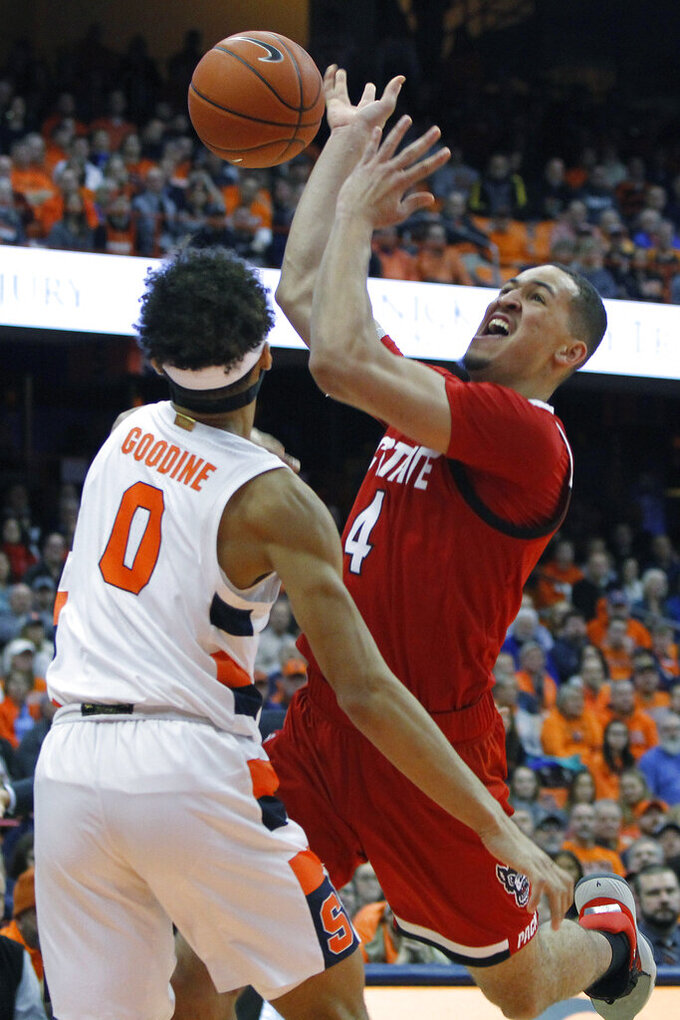 North Carolina State's Jericole Hellems, right, shoots over Syracuse's Brycen Goodine, left, in the first half of an NCAA college basketball game in Syracuse, N.Y., Tuesday, Feb. 11, 2020. (AP Photo/Nick Lisi)
