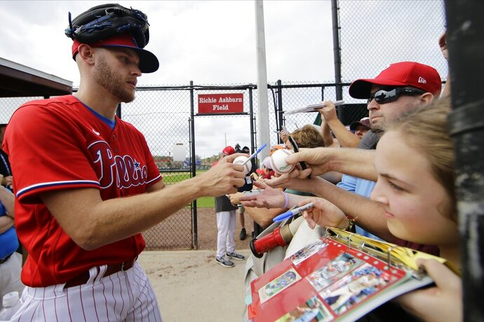 FILE - In this Feb. 14, 2020, file photo, Philadelphia Phillies' Zack Wheeler, left, gives autographs during a spring training baseball workout in Clearwater, Fla. Wheeler's last start before his 30th birthday could have come against his former team. Wheeler, who struck out 24% of the batters he faced last season with the Mets, left New York in free agency last winter for a $118 million, five-year deal with the NL East rival Phillies.(AP Photo/Frank Franklin II, File)