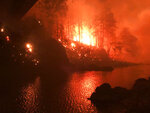 This photo was taken by Don Myron as he shielded himself with a green plastic chair from a huge, deadly wildfire as he sheltered from the flames on a rock in the middle of Little North Santiam River after fleeing his home in Lyons, Ore., Monday, Sept. 7, 2020.