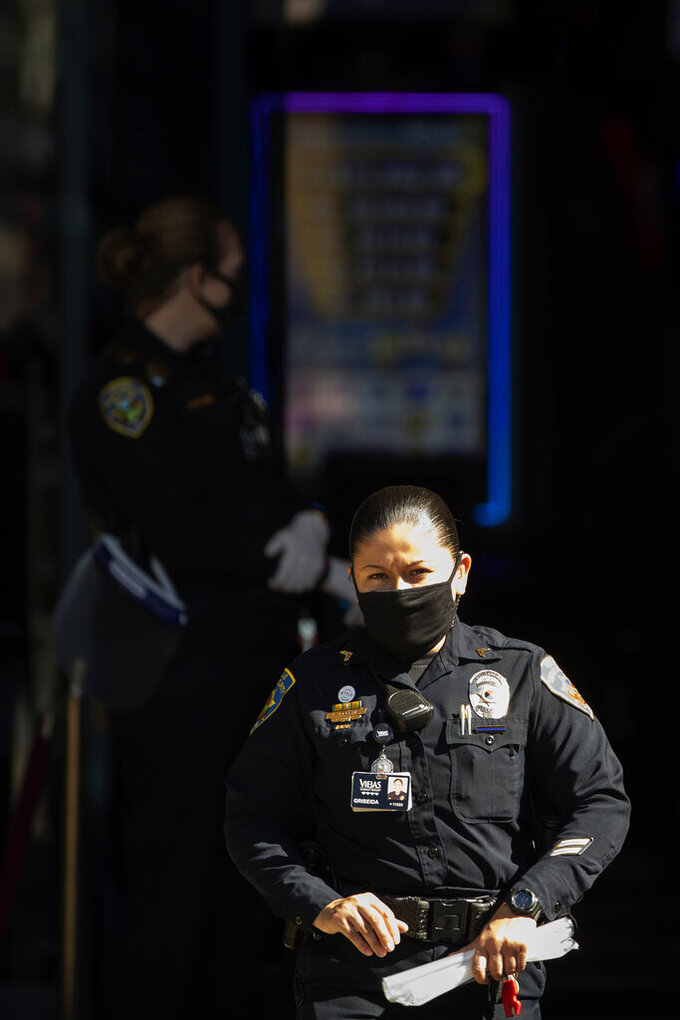 Security officials wear masks at the entrance to the Viejas Casino and Resort as it reopens Monday, May 18, 2020, in Alpine, Calif. The casino is one of several on tribal lands in Southern California set to reopen this week. (AP Photo/Gregory Bull)