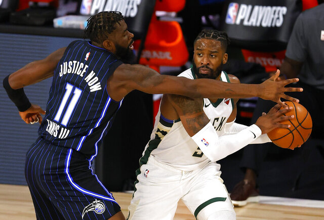 Orlando Magic's James Ennis III (11)  defends against Milwaukee Bucks' Wesley Matthews (9) during Game 3 of an NBA basketball first-round playoff series, Saturday, Aug. 22, 2020, in Lake Buena Vista, Fla. (Mike Ehrmann/Pool Photo via AP)