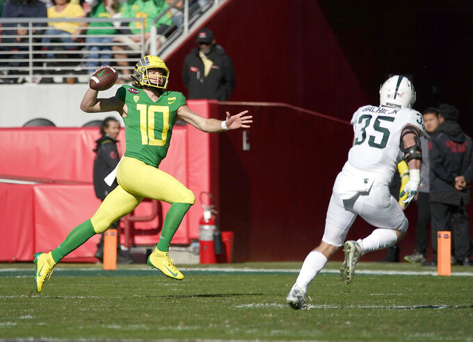 Oregon quarterback Justin Herbert (10) scrabbles for a first down against Michigan State linebacker Joe Bachie (35) during the first half of the Redbox Bowl NCAA college football game Monday, Dec. 31, 2018, in Santa Clara, Calif. (AP Photo/Tony Avelar)