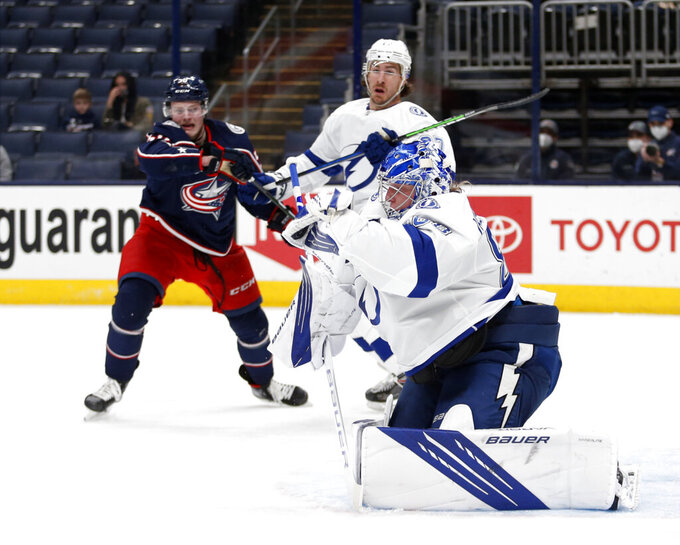 Tampa Bay Lightning goalie Andrei Vasilevskiy, right, stops a shot in front of Columbus Blue Jackets forward Eric Robinson, left, and Lightning defenseman Ryan McDonagh during the second period of an NHL hockey game in Columbus, Ohio, Thursday, April 8, 2021. (AP Photo/Paul Vernon)