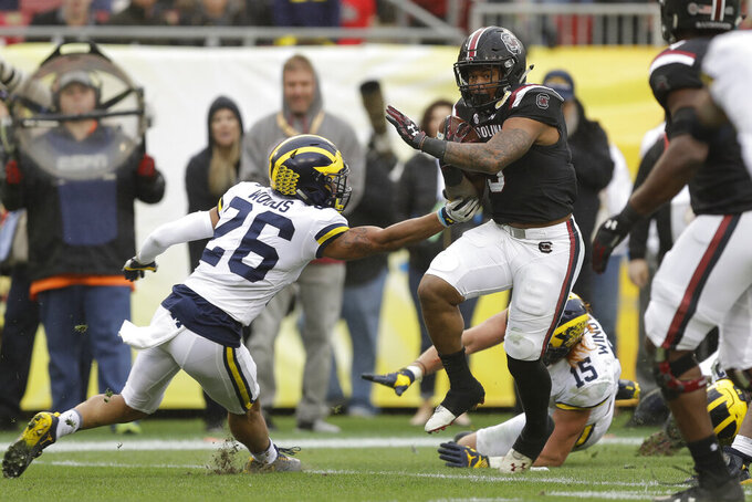 FILE - In this Jan. 1, 2018, file photo, South Carolina running back Rico Dowdle (5) runs past Michigan defensive back J'Marick Woods (26) and defensive lineman Chase Winovich (15) on a 7-yard touchdown run during the second half of the Outback Bowl NCAA college football game in Tampa, Fla. South Carolina's Will Muschamp believes he's got the strongest, deepest and most talented team in his four seasons as the Gamecocks' coach. (AP Photo/Chris O'Meara, File)