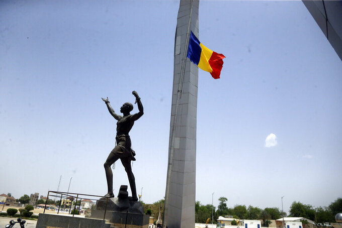 """A Chadian flag flies at half-staff at the """"Place de Le Nation"""" (Monument of independence) park in N'Djamena, Chad, Monday, April 26, 2021. Chad's military transitional government said Sunday it will not negotiate with the rebels blamed for killing the country's president of three decades, raising the specter that the armed fighters might press ahead with their threats to attack the capital. (AP Photo/Sunday Alamba)"""