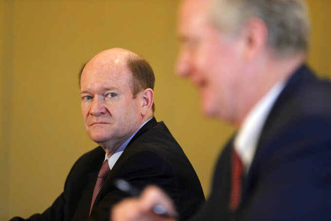 U.S. Senator Chris Coons, left, looks at Senator Chris Van Hollen during a press briefing in Abu Dhabi, United Arab Emirates, Monday, May 3, 2021. Top Biden administration officials and U.S. senators crisscrossed the Middle East on Monday, seeking to assuage growing unease among key Gulf Arab partners over America's rapprochement with Iran and other policy shifts. (AP Photo/Kamran Jebreili)