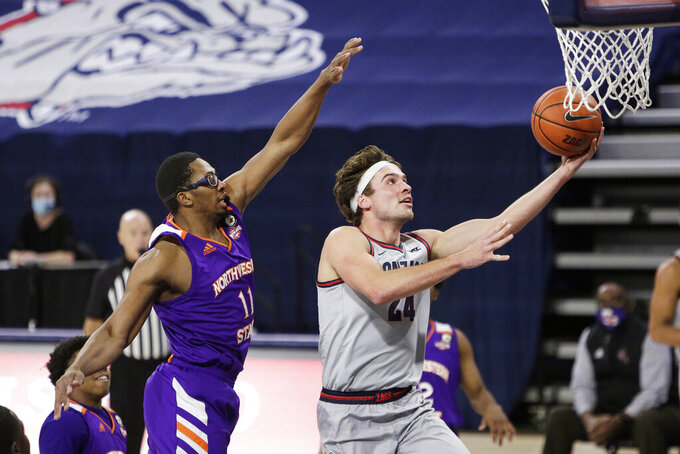 Gonzaga forward Corey Kispert (24) shoots in front of Northwestern State forward Jamaure Gregg (11) during the first half of an NCAA college basketball game in Spokane, Wash., Tuesday, Dec. 22, 2020. (AP Photo/Young Kwak)